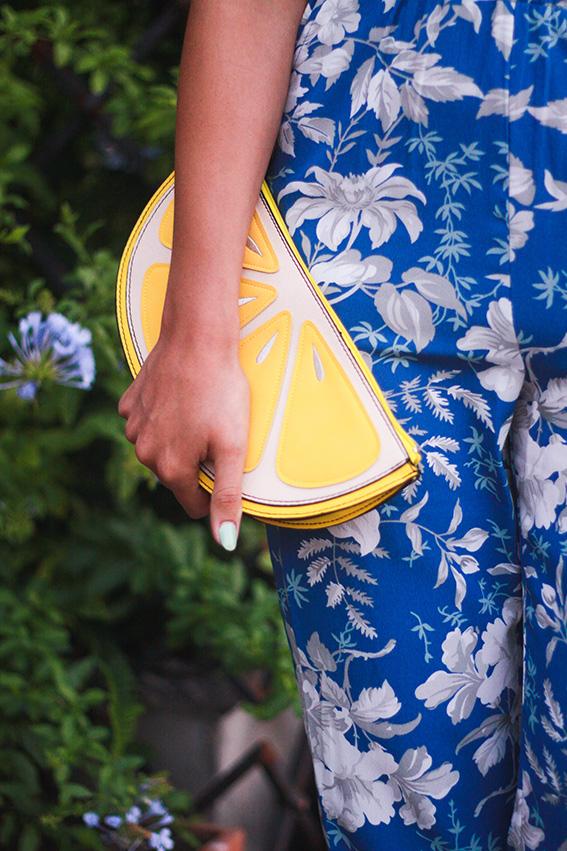 Bar Vitelli, Savoca en Sicile, bar où une scène du Parrain a été tournée: combinaison fleurie tropicale bleue et blanche, chaussures compensées et pochette Newlook en forme de citron