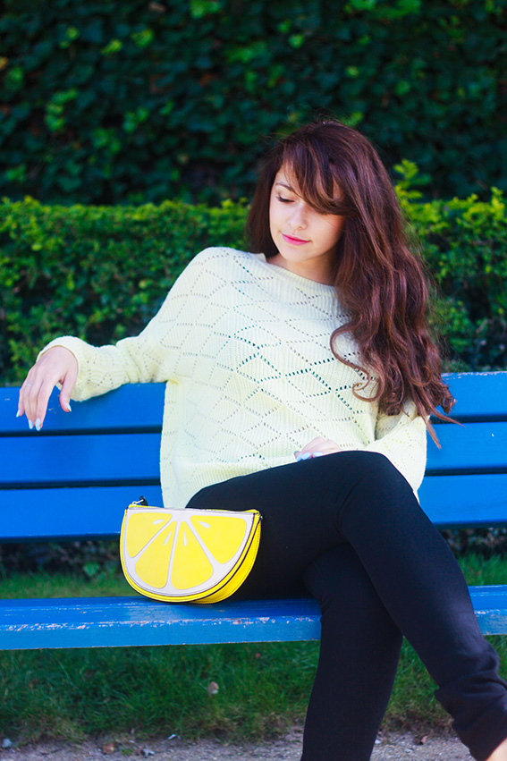 Blogueuse mode française, french fashion blogger. Assise sur un banc, jean slim noir, pull jaune, ballerines jaunes, pochette citron, lemon clutchbag Newlook